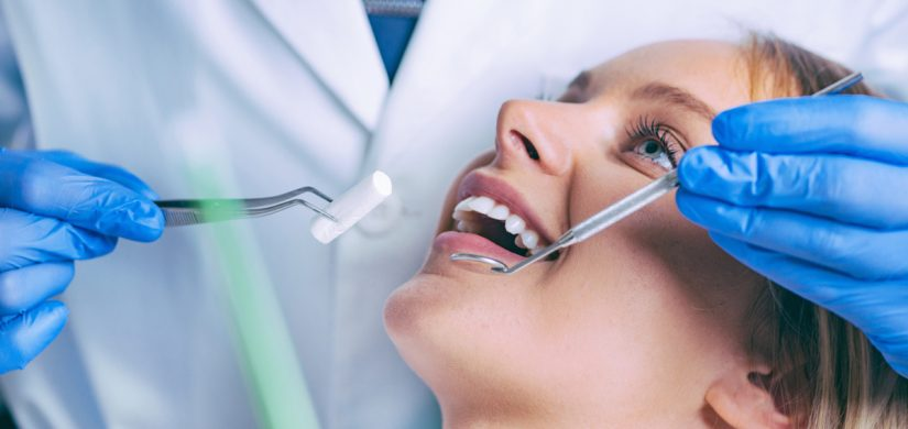 dentist-working-with-young-female-patient-GKC5MLH