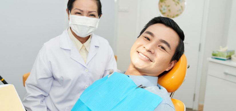 smiling-ethnic-dentist-and-man-in-dental-chair-CNVS7GE